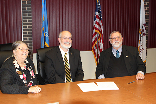 Redlands Community College Chief Academic Officer Rose Marie Moore (left), Cameron University President John McArthur (middle) and Redlands Community College President Jack Bryant sign an articulation agreement