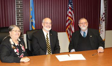 Redlands Community College Chief Academic Officer Rose Marie Moore (left), Cameron University President John McArthur (middle) and Redlands Community College President Jack Bryant sign an articulation agreement.