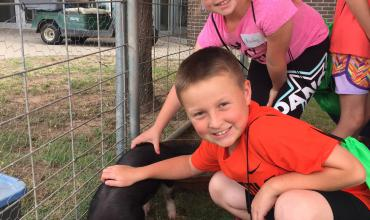 Redlands Summer Kids' College students pet the farm animals brought by AgVocates.